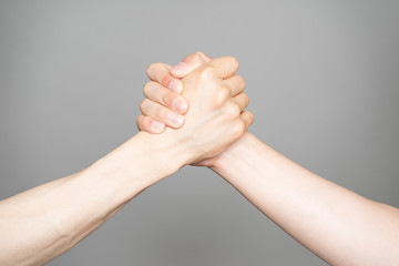 Hand holding hand isolated over gray background - Friendship, Sh