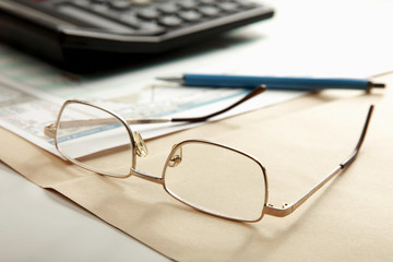 Calculator , folder with paper, pen and glasses