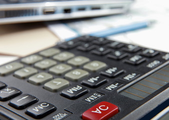 Calculator, pen, folder with documents, laptop