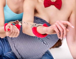 Sexy lesbian women with handcuffs  in erotic game.