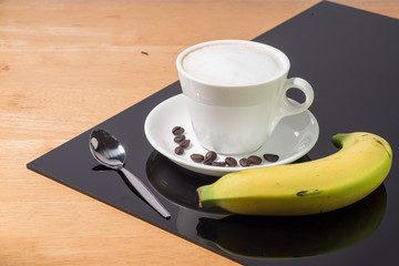 A cup of coffee in a white cup with banana and spoon