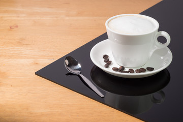 A cup of coffee in a white cup and spoon