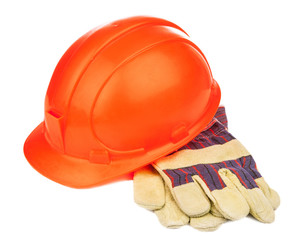 A construction hat and heavy duty gloves isolated over white