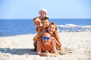 Mother and father with three children on the beach.