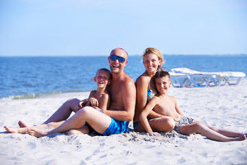 Smiling mother and father with children on the beach.