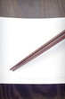 Brown wood chopstick on empty white plate