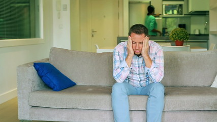 Man having headache and sitting on the sofa