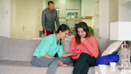 Woman giving present to her friend on the sofa