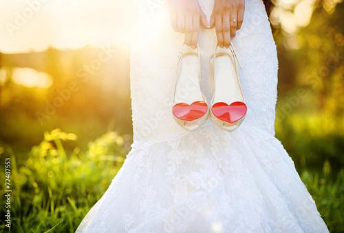 Bride holding wedding shoes - 72487553