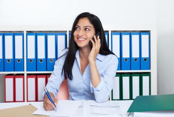 Lachende Frau aus der Türkei im Büro am Handy