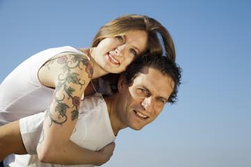 Chica rubia con tatuaje abrazando a su chico