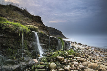 Landscape image of wide waterfall flowing onto rocky beach at su