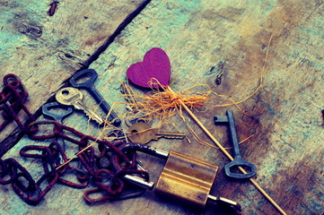 Keys and padlock on a wooden background