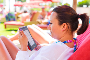 Woman reading on electronic book on summer holidays