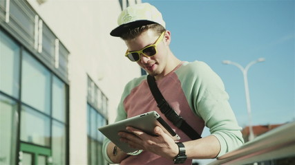 Young smiling man in the city looking at his tablet, outdoors.