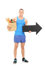 Male athlete holding a grocery bag and an arrow
