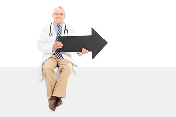 Mature doctor holding an arrow and sitting on a panel