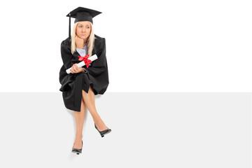 Sad female graduate holding a diploma