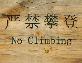 prohibition sign in chinese and english : no climbing