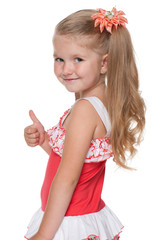 Little girl with her thumb up looks back