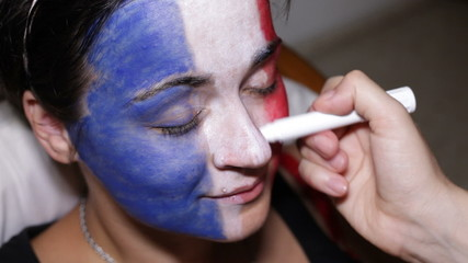 Closeup of a woman face painting flag of France.