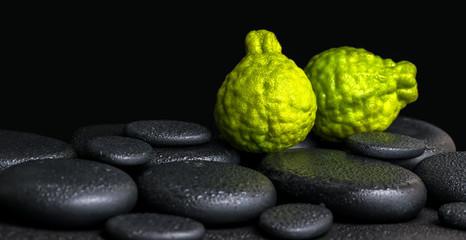 Aromatic spa concept of bergamot fruits on zen basalt black ston
