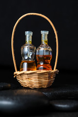 Aromatic spa concept of bottles essential oil in basket on black