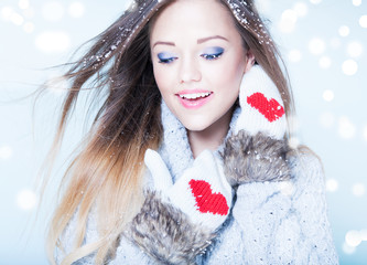 Young woman wearing winter gloves covered with snow flakes