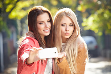 Friends making selfie. Two beautiful young women making selfie a