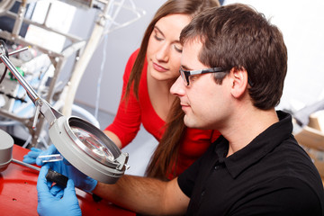 Scientists working with magnifier