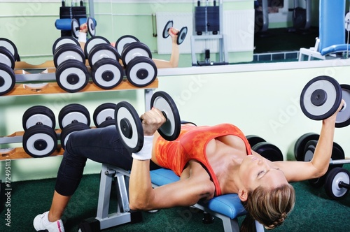 Fototapeta Beautiful muscular woman exercising in a gym