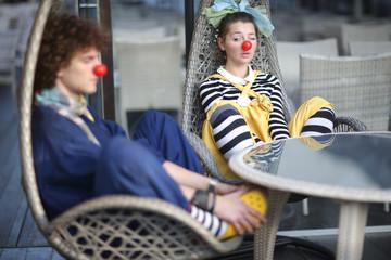 Spy on fellow, clowns having rest in rattan swing chair