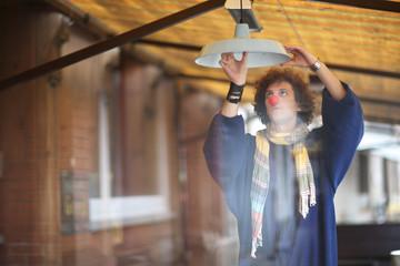 Curious clown unscrew the light bulb