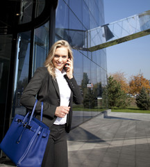 Businesswoman using a mobile phone on the street, cityscape in t