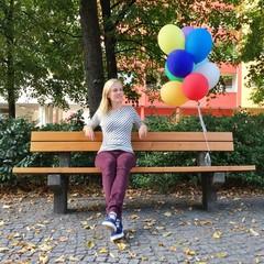 Mädchen sitzt auf Bank mit Ballons