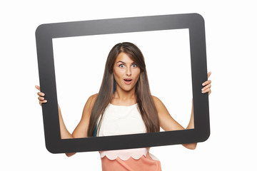 Excited woman looking through tablet frame