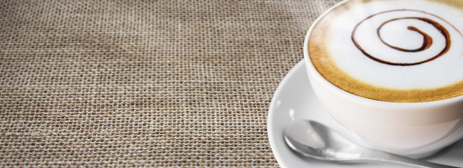 Coffee cup and saucer on sackcloth background