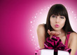 Christmas woman blowing kiss with gift box and red bow
