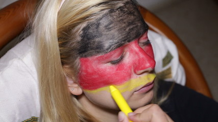 Closeup of a woman face painting flag of Germany.