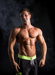 Attractive shirtless muscular man smiling at camera