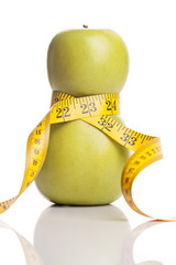 Concept for a diet. Apple wrapped with measuring tape