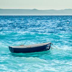 little blue boat is seesawing on waves in mediterrean