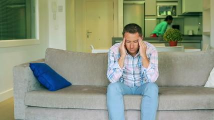 Man having headache and his girlfriend bringing him pills