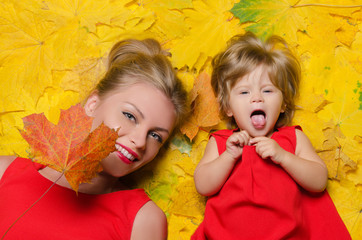 girl and young woman in autumn leaves