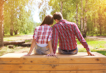 Pretty young modern couple in love resting outdoors in the park