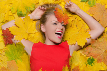 smiling woman in yellow autumn leaves