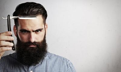 Portrait of brutal man with vintage straight razor