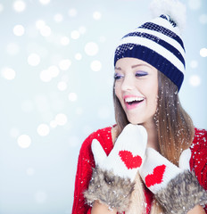 Woman wearing winter clothes covered with snowflakes.