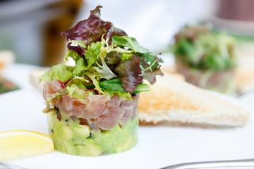 Tuna and avocado tartar with toast and lemon.