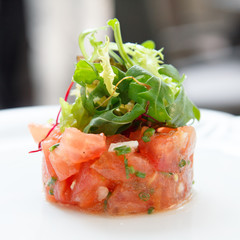 Tomato tartare topped with green salad.